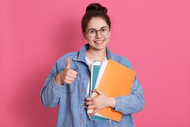Jeune étudiante femme portant veste en jean et lunettes, tenant des dossiers colorés et montrant le pouce vers le haut sur rose