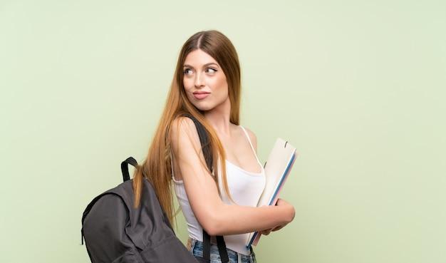 Jeune étudiante femme sur vert isolé rire