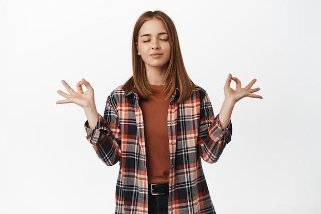 Jeune étudiante ferme les yeux, méditant, geste de yoga de la paix, se tenant la main dans le signe du mudra zen, se tenant patiemment debout, debout contre le mur blanc