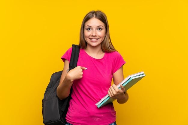 Jeune étudiante fille sur un mur jaune isolé avec une expression faciale surprise