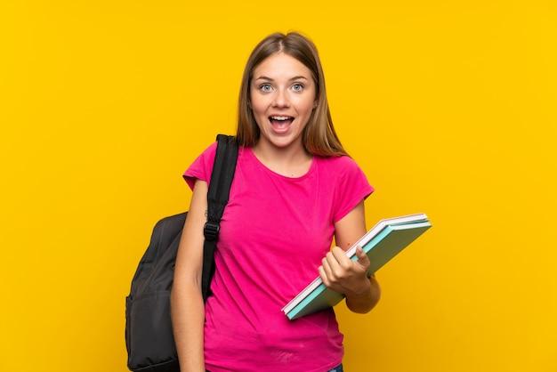 Jeune étudiante fille sur un mur jaune isolé avec surprise et une expression faciale choquée