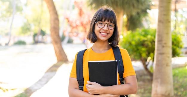 Jeune étudiante gagne un parc tenant un cahier