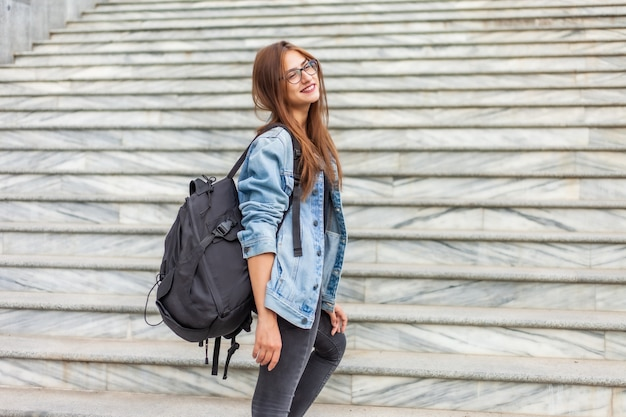 Jeune étudiante gaie dans une veste en jean et des lunettes avec un grand sac à dos monte les escaliers de la ville. concept jeunesse
