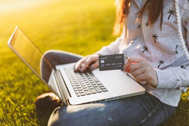 Jeune étudiante heureuse avec carte de crédit. femme assise sur un terrain en herbe, travaillant sur un ordinateur portable dans un parc de la ville sur une pelouse d'herbe verte à l'extérieur. bureau mobile. concept d'entreprise indépendant.
