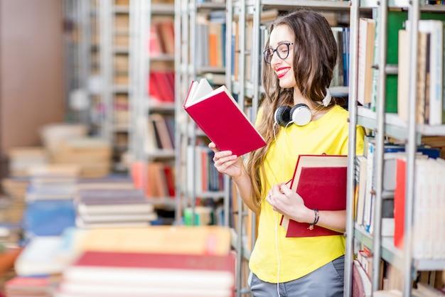 Jeune étudiante heureuse et enthousiaste lisant des livres à l'ancienne bibliothèque