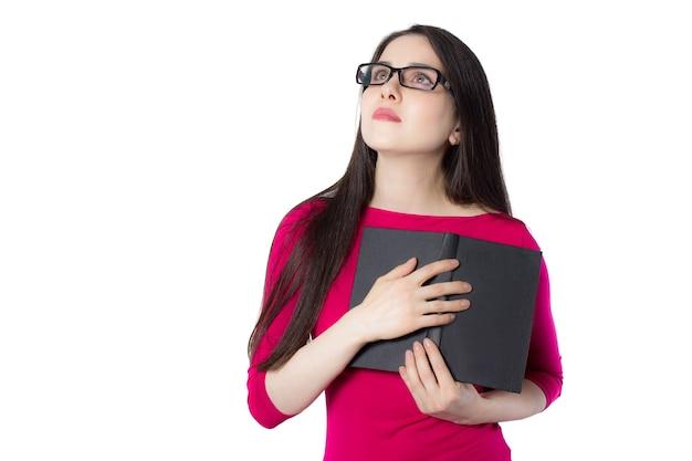 Jeune étudiante intelligente en chemise rouge et lunettes en appuyant sur un livre noir sur son cœur, regardant au-dessus sur fond blanc, idée de concept de femme de connaissance