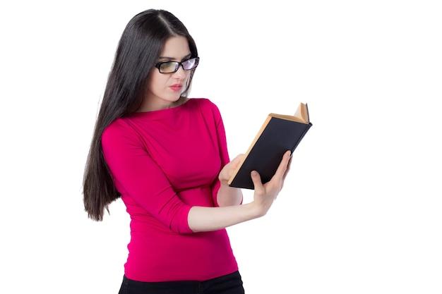 Jeune étudiante intelligente en chemise rouge et lunettes lisant un livre noir tenant dans une main, sur fond blanc, doutez l'idée de concept de femme