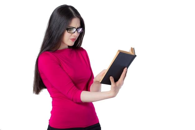 Jeune étudiante intelligente en chemise rouge et lunettes lisant un livre noir tenant dans une main, sur fond blanc, idée de concept de femme incompréhensible