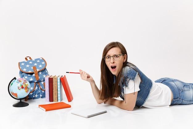 Jeune étudiante irritée en vêtements en jean, lunettes écrivant des notes sur un cahier et allongée près du globe, sac à dos, livre d'école isolé