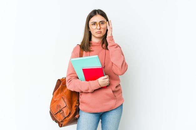 Jeune étudiante isolée sur bakcground blanc concentré sur une tâche, gardant l'index pointant la tête.
