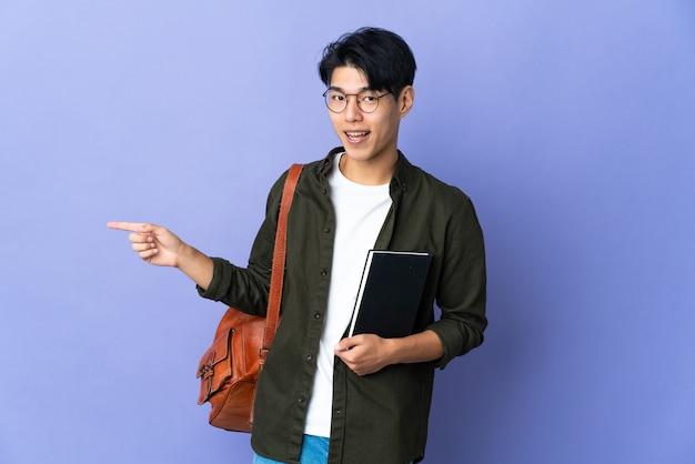 Jeune étudiante isolée du doigt pointé sur le côté et présentant un produit