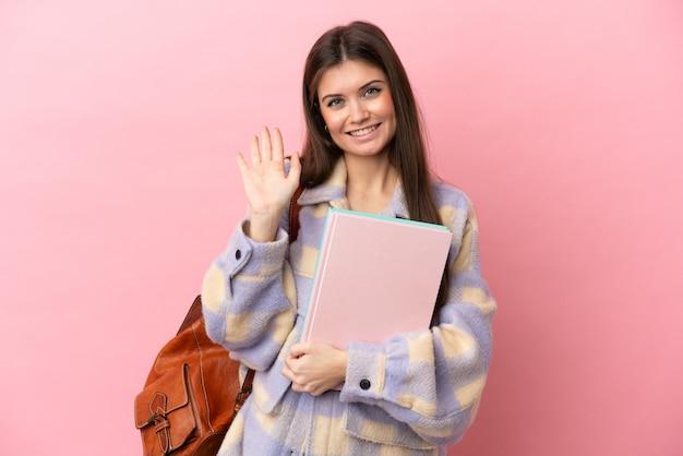 Jeune étudiante isolée sur fond rose saluant avec la main avec une expression heureuse