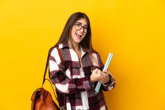 Jeune étudiante isolée sur un mur jaune célébrant une victoire
