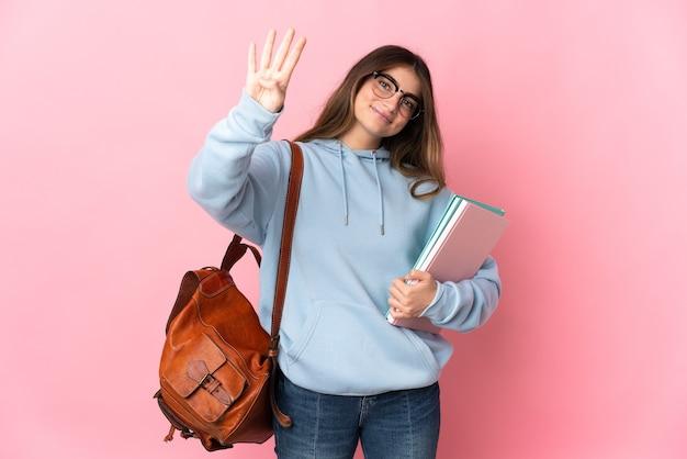 Jeune étudiante isolée sur rose heureux et comptant quatre avec les doigts