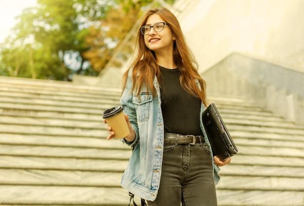 Jeune étudiante joyeuse dans une veste en jean et des lunettes descend les escaliers avec un ordinateur portable et une tasse de café dans les mains dans la ville