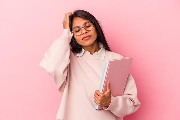 Jeune étudiante latine isolée sur fond rose étant choquée, elle s'est souvenue d'une réunion importante.