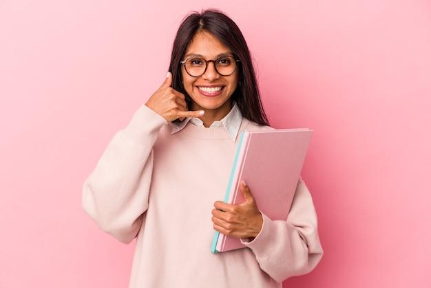 Jeune étudiante latine isolée sur fond rose montrant un geste d'appel de téléphone portable avec les doigts.