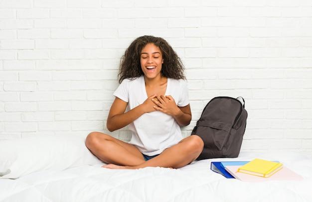 Jeune étudiante sur le lit en riant en gardant les mains sur le coeur