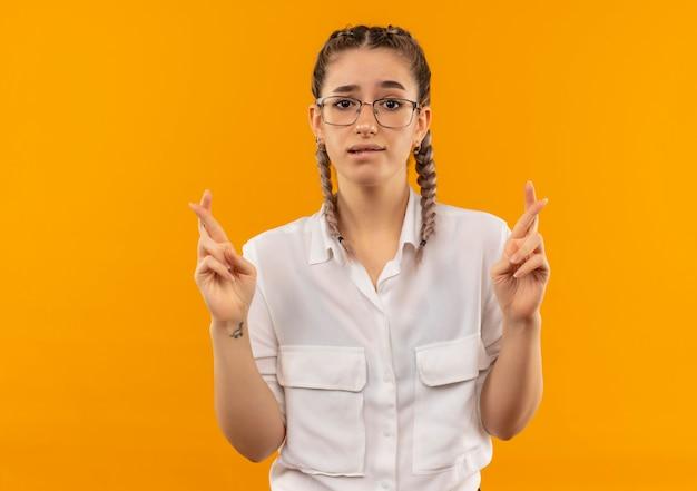 Jeune étudiante à lunettes avec des nattes en chemise blanche à l'avant émotive et inquiète faisant souhait désirable mordre la lèvre et croiser les doigts debout sur le mur orange