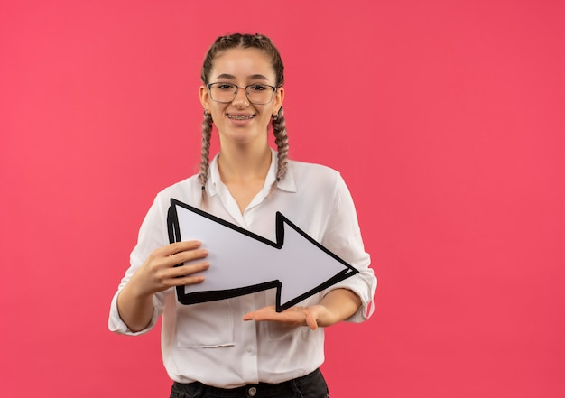 Jeune étudiante à lunettes avec des nattes en chemise blanche tenant une flèche blanche à l'avant souriant joyeusement debout sur un mur rose