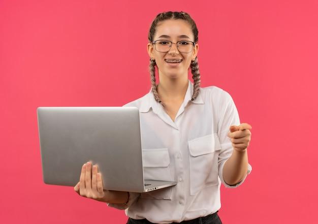 Jeune étudiante à lunettes avec des nattes en chemise blanche tenant un ordinateur portable pointant avec le doigt vers l'avant souriant joyeusement debout sur le mur rose