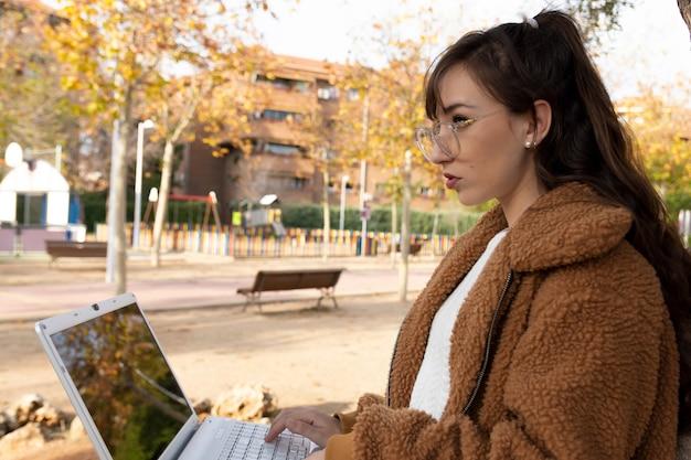 Jeune étudiante avec des lunettes travaillant avec son ordinateur portable dans le parc.