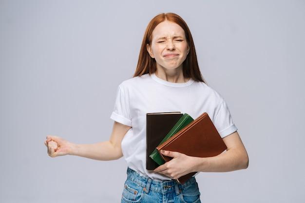 Jeune étudiante mécontente confuse tenant un livre et criant en regardant la caméra