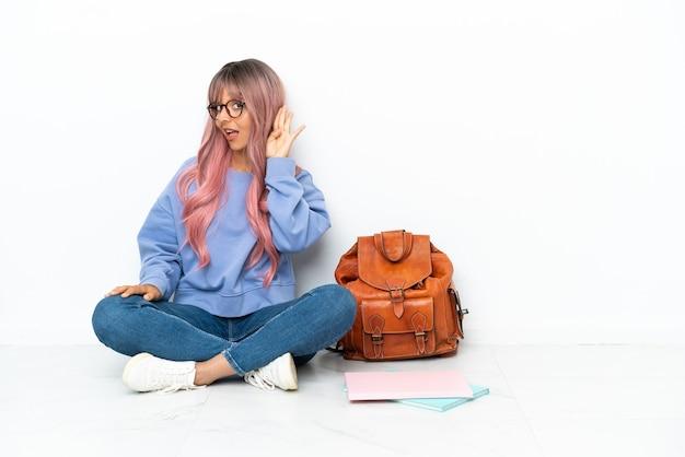 Jeune étudiante métisse femme aux cheveux roses assis sur le sol isolé sur fond blanc écoutant quelque chose en mettant la main sur l'oreille