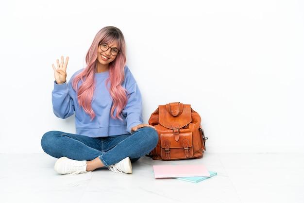 Jeune étudiante métisse femme aux cheveux roses assis sur le sol isolé sur fond blanc heureux et comptant quatre avec les doigts