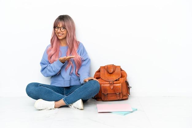 Jeune étudiante métisse femme aux cheveux roses assis sur le sol isolé sur fond blanc présentant une idée tout en regardant en souriant vers