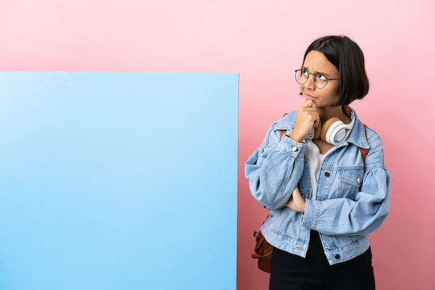 Jeune étudiante métisse femme avec une grande bannière sur fond isolé ayant des doutes