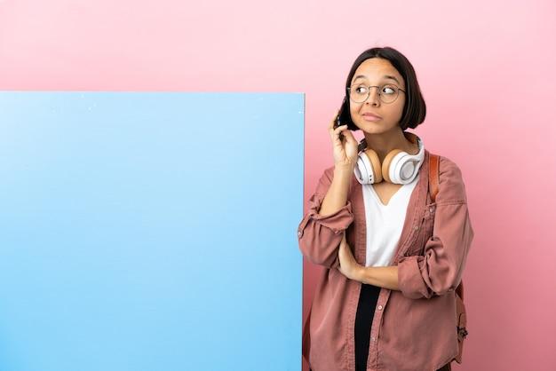 Jeune étudiante métisse femme avec une grande bannière sur fond isolé en gardant une conversation avec le téléphone mobile