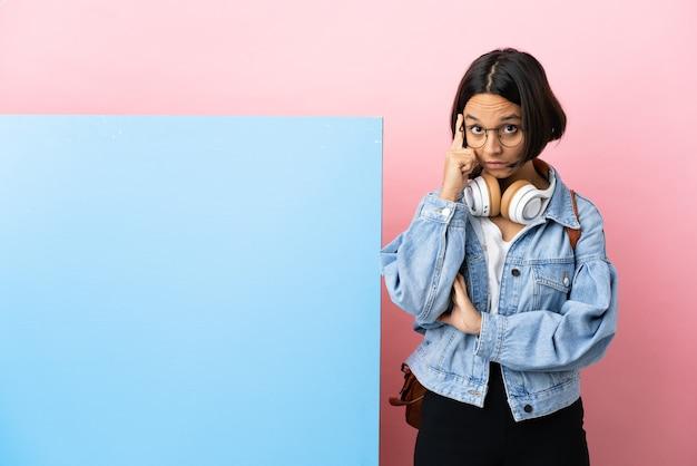 Jeune étudiante métisse femme avec une grande bannière sur fond isolé pensant une idée