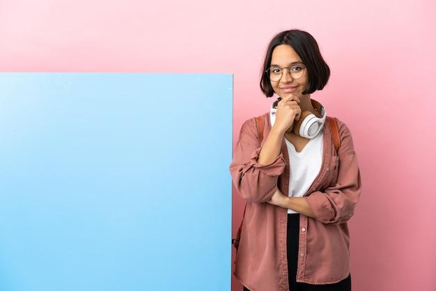 Jeune étudiante métisse femme avec une grande bannière sur fond isolé de la pensée