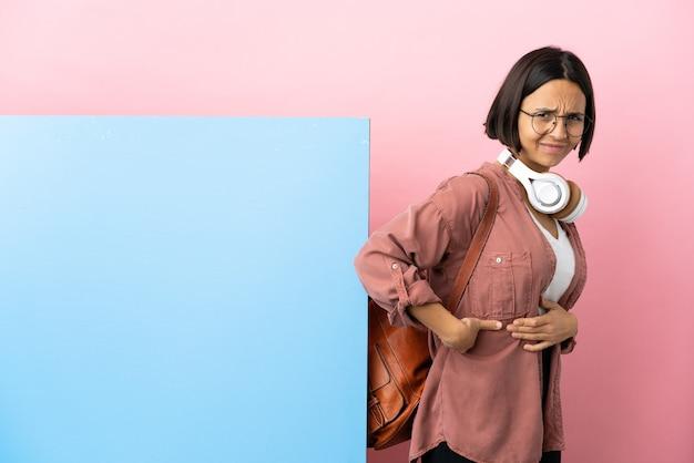 Jeune étudiante métisse femme avec une grande bannière sur fond isolé souffrant de maux de dos pour avoir fait un effort