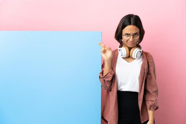 Jeune étudiante métisse femme avec une grande bannière isolée sur fond avec les doigts qui se croisent et souhaitant le meilleur