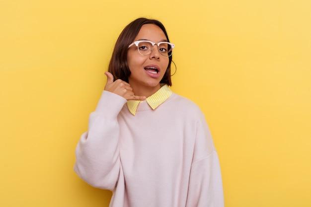 Jeune étudiante métisse femme isolée sur fond jaune montrant un geste d'appel de téléphone mobile avec les doigts.