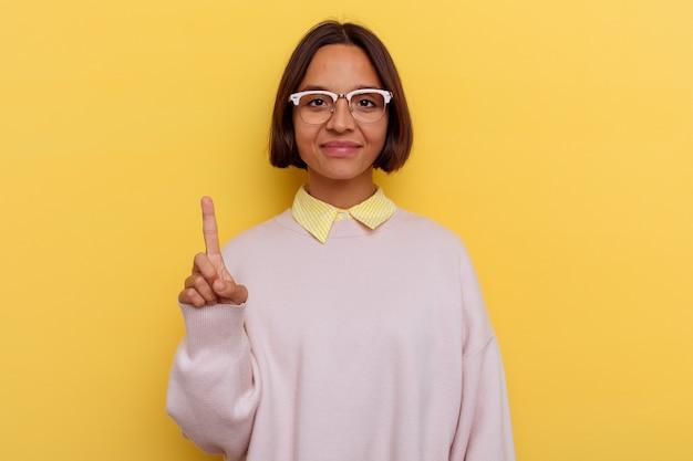 Jeune étudiante métisse femme isolée sur fond jaune montrant le numéro un avec le doigt.