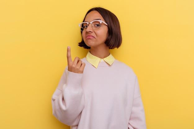 Jeune étudiante métisse femme isolée sur fond jaune pointant avec le doigt sur vous comme si vous invitiez à vous rapprocher.