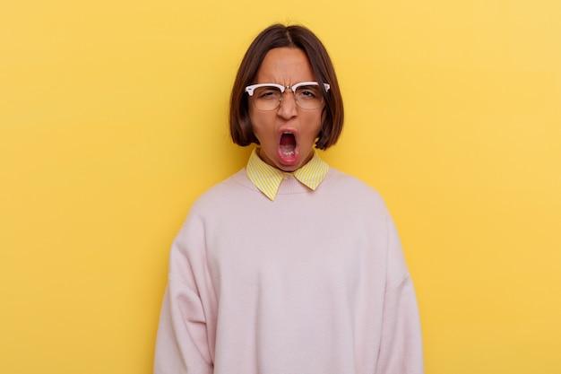 Jeune étudiante métisse isolée sur fond jaune criant très en colère et agressif.