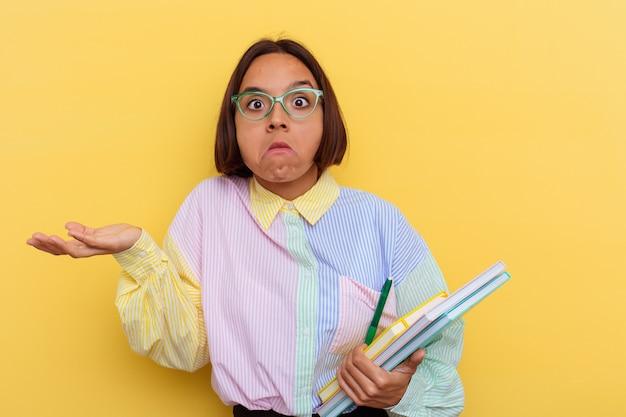 Jeune étudiante métisse isolée sur fond jaune hausse les épaules et les yeux ouverts confus.