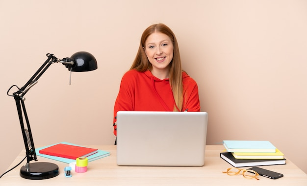 Jeune étudiante en milieu de travail avec un ordinateur portable en gardant les bras croisés en position frontale