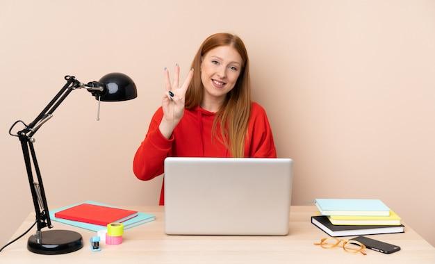 Jeune étudiante en milieu de travail avec un ordinateur portable heureux et en comptant trois avec les doigts