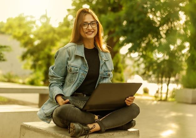 Jeune étudiante moderne dans une veste en jean assis sur les escaliers avec ordinateur portable. apprentissage à distance. concept de jeunesse moderne.