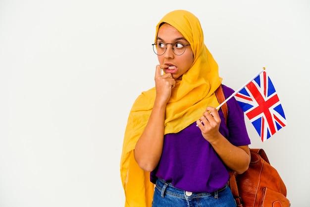 Jeune étudiante musulmane isolée sur un mur blanc détendu penser à quelque chose en regardant un espace de copie