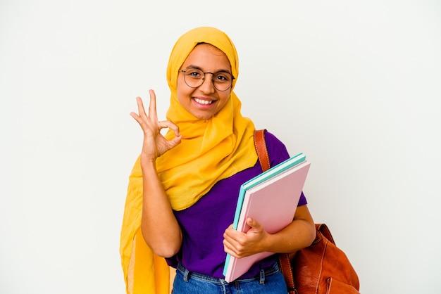Jeune étudiante musulmane portant un hijab isolé sur fond blanc joyeux et confiant montrant le geste ok.