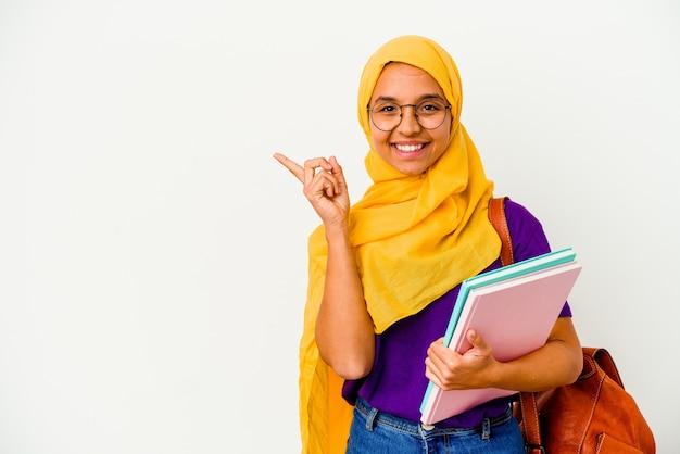 Jeune étudiante musulmane portant un hijab isolé sur fond blanc souriant et pointant de côté, montrant quelque chose à l'espace vide.