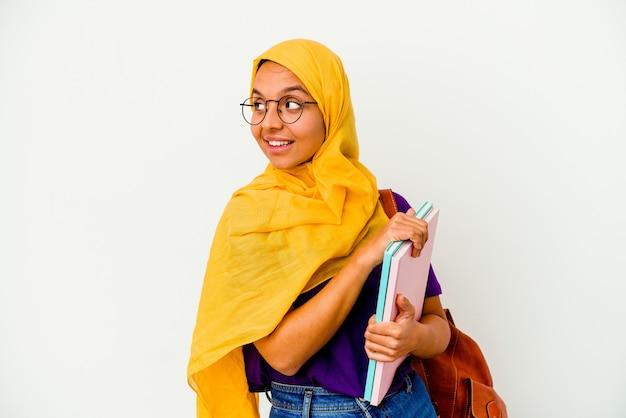 Jeune étudiante musulmane portant un hijab isolé sur un mur blanc regarde de côté souriant, gai et agréable.