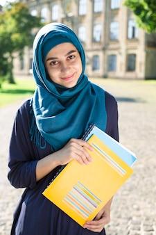 Jeune étudiante musulmane souriante tenant des livres debout près du collège. heureuse jeune fille arabe en hijab. femme asiatique sur la formation.