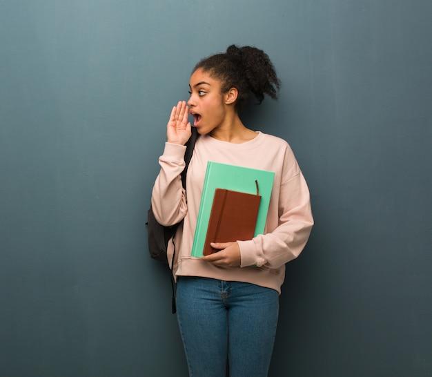Jeune étudiante noire chuchotant une rumeur de potins. elle tient des livres.
